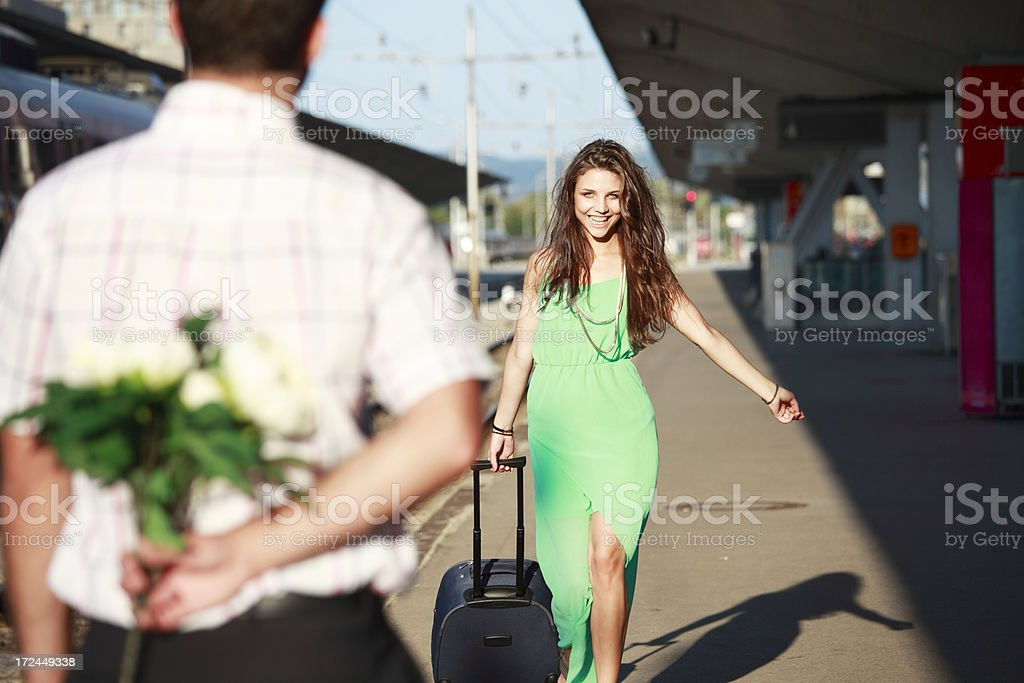 Woman met by boyfriend with flowers at the train station royalty-free stock photo