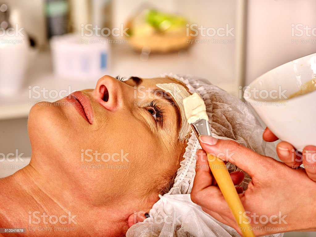 Woman middle-aged gets face massage in spa salon stock photo