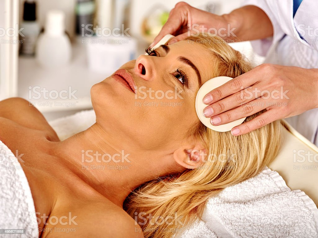 Woman middle-aged in spa salon and beautician cleanses face stock photo