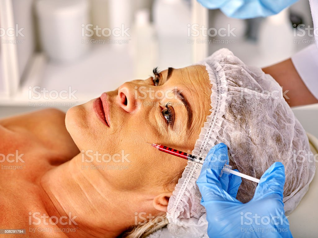 Woman middle-aged in spa salon  giving botox injections stock photo
