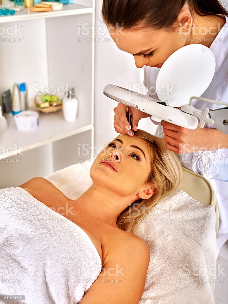 Woman middle-aged in spa salon. Tweezing eyebrow by beautician stock photo