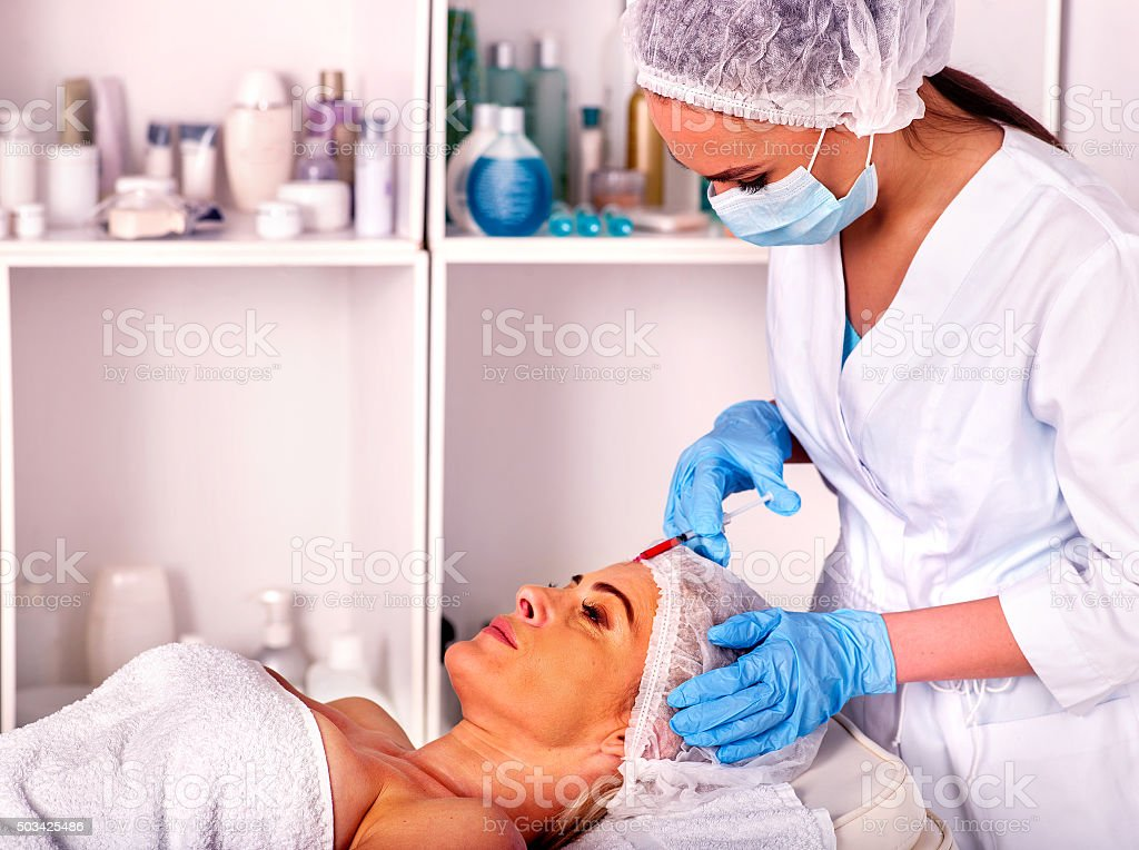 Woman middle-aged in spa salon with beautician. Female giving stock photo