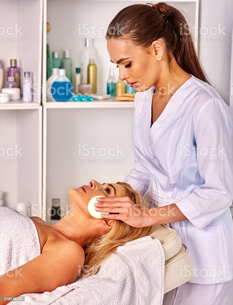 Woman middle-aged take face cleaning in spa salon stock photo