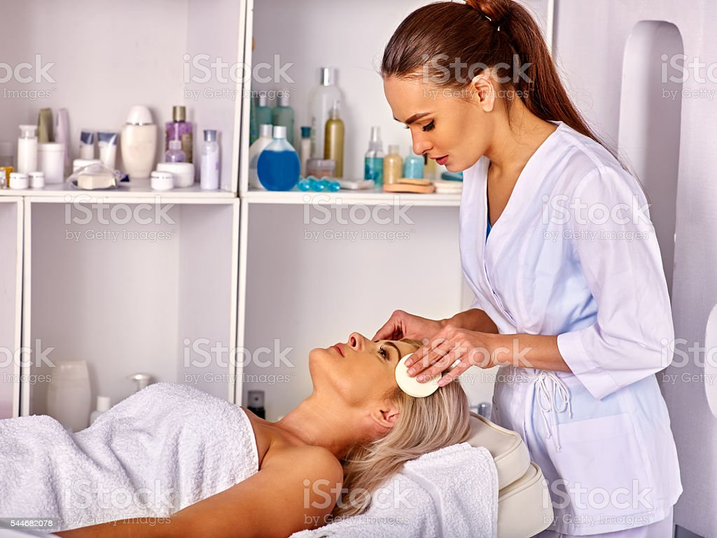 Woman middle-aged take face cleaning in spa salon. stock photo