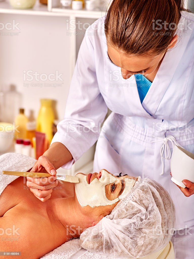 Woman middle-aged take face massage in spa salon stock photo
