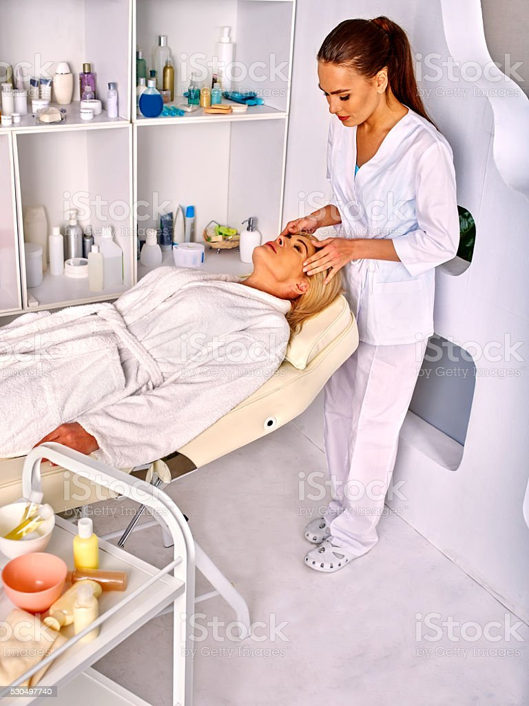 Woman middle-aged take face massage in spa salon. stock photo