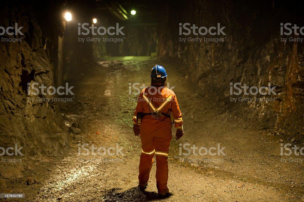 Woman Mine Worker under ground in a tunnel. stock photo