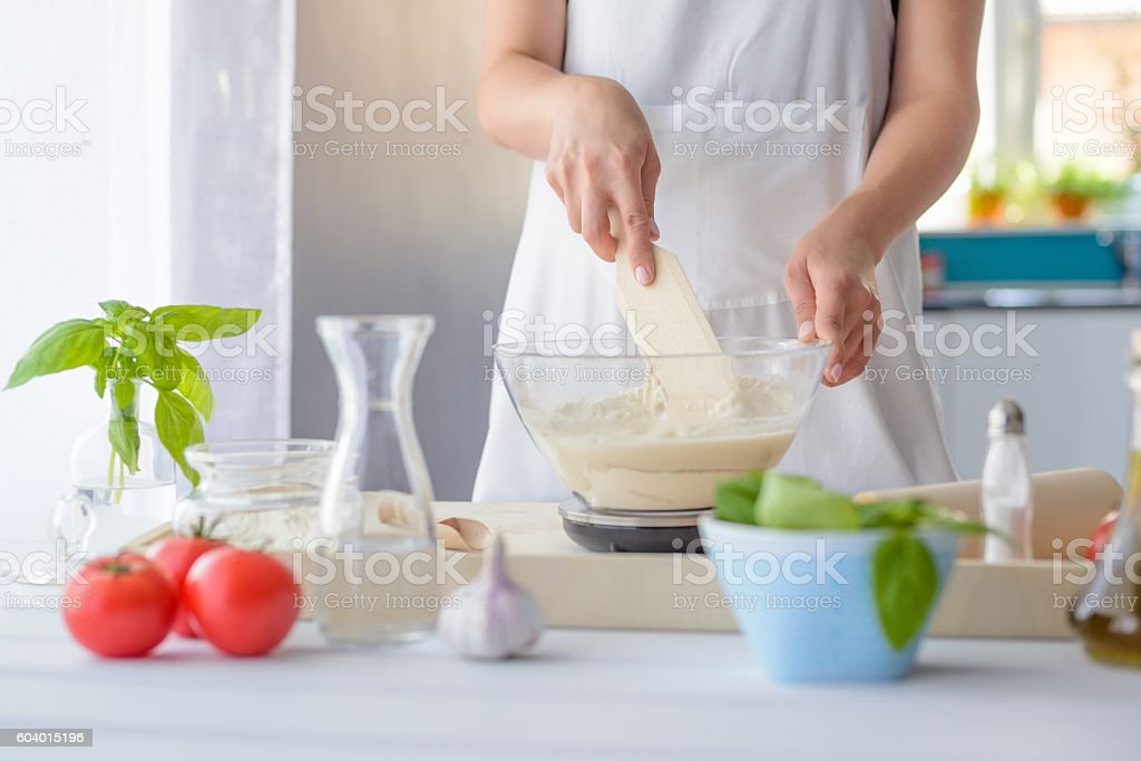 Woman mixing pizza dough with wooden spatula. stock photo