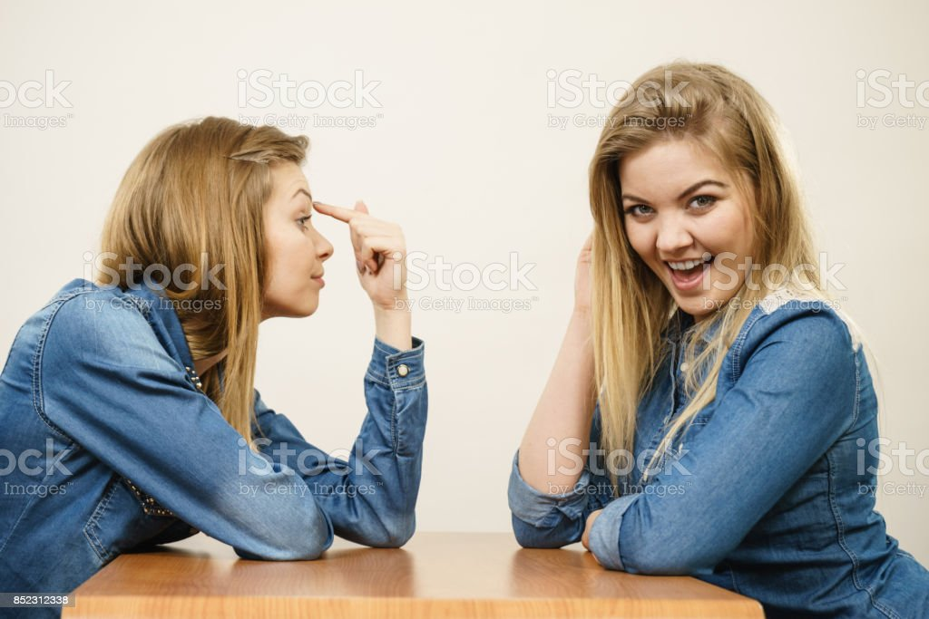 Woman mocking her confident friend stock photo