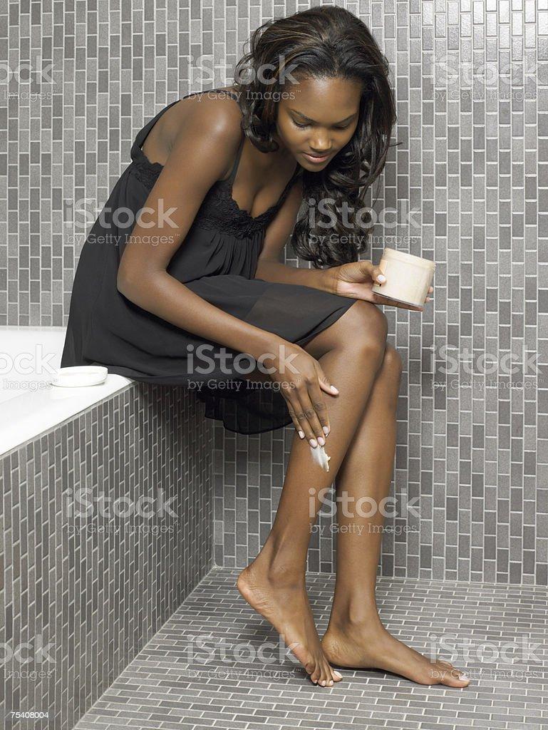 Woman moisturising her leg royalty-free stock photo