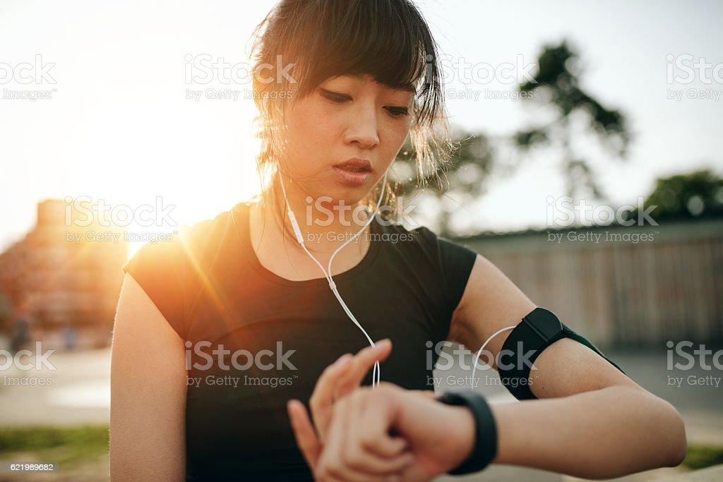 Woman monitoring her progress on smartwatch stock photo