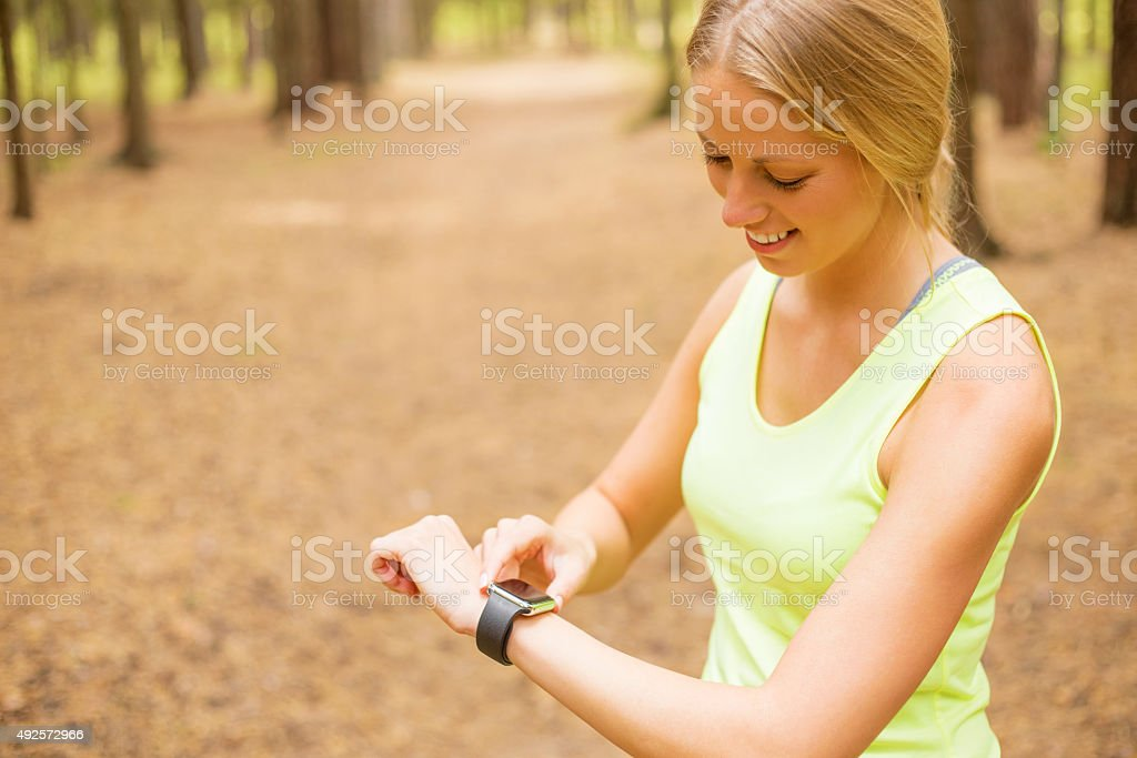 Woman monitoring her pulse on smartwatch stock photo