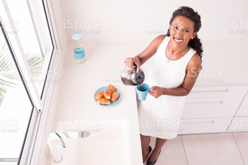 High angle view of young beautiful woman pouring cup of coffee,...