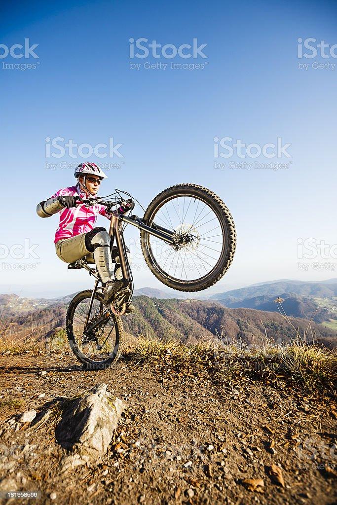 Woman mountainbiker on mountain bike riding wheelie royalty-free stock photo