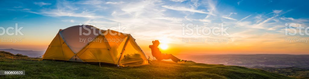 Woman mountaineer relaxing beside tent idyllic summer sunset camping panorama stock photo