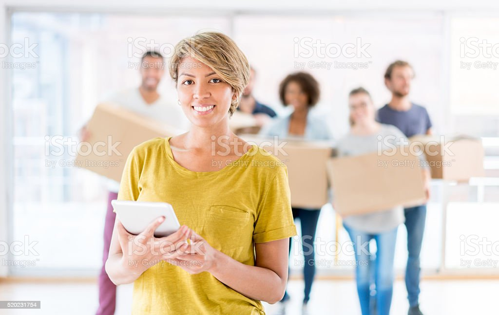 Woman moving and using a tablet stock photo
