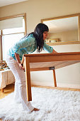 Woman moving furniture in her home