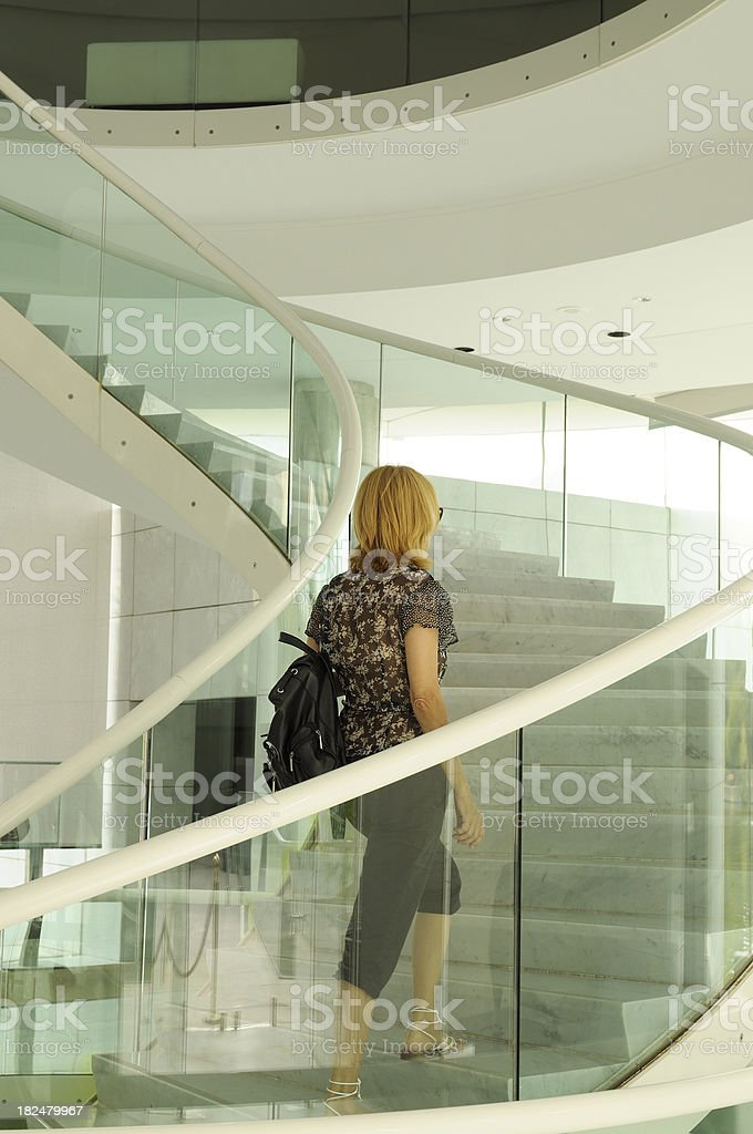 Woman Moving Up Contemporary Spiral Staircase royalty-free stock photo