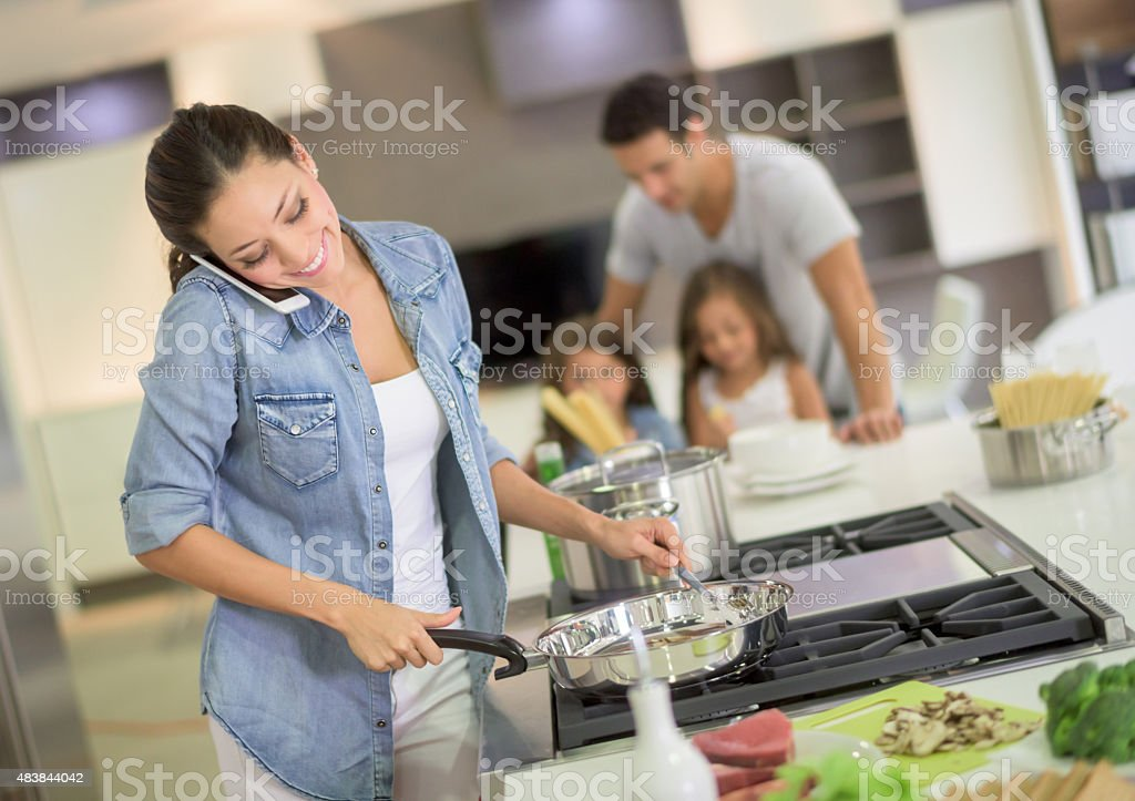 Woman multitasking at home stock photo