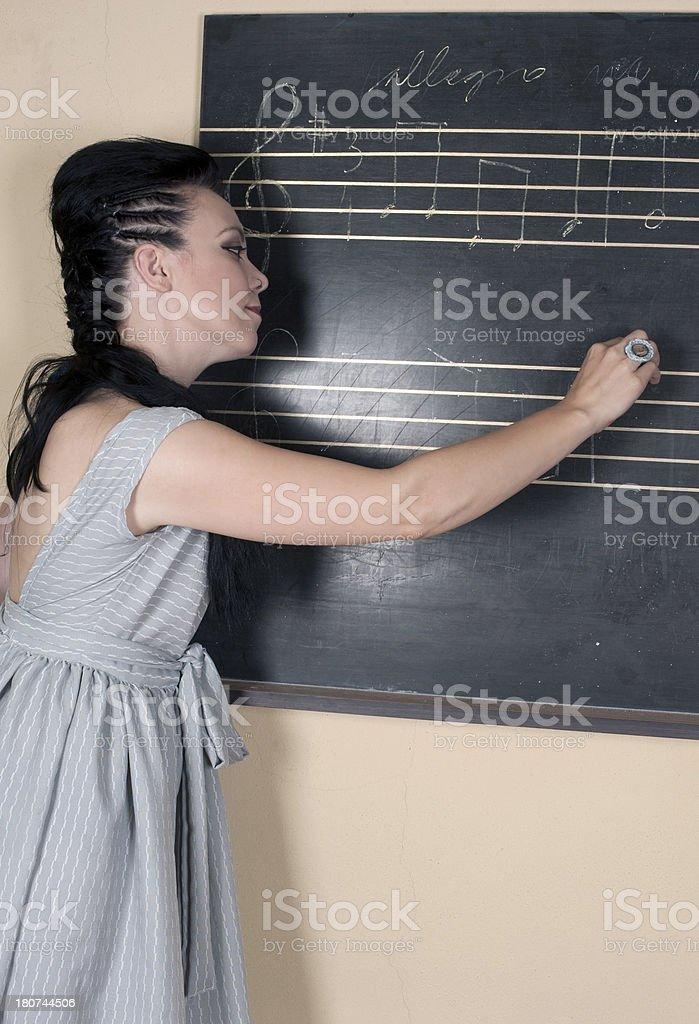 Woman Music Teacher Writing at Blackboard stock photo