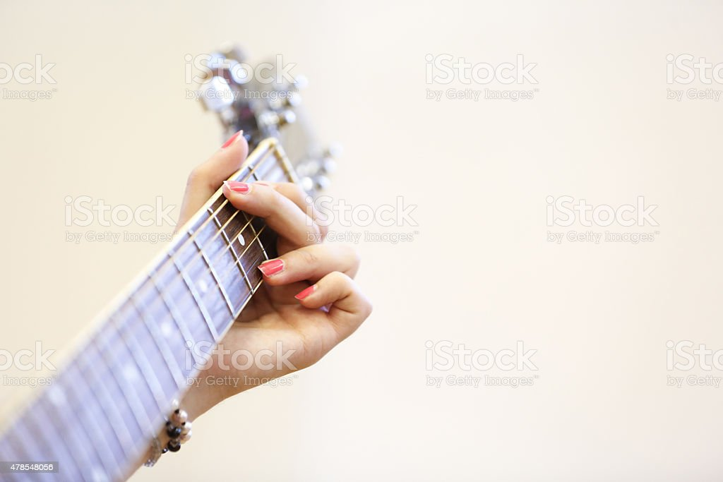 Woman musician holding a guitar, playing a G chord stock photo
