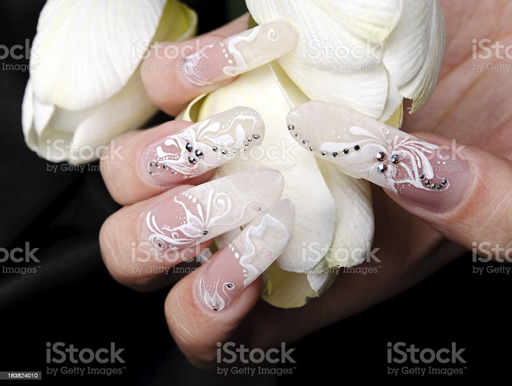 woman hand with false nails holding petals.