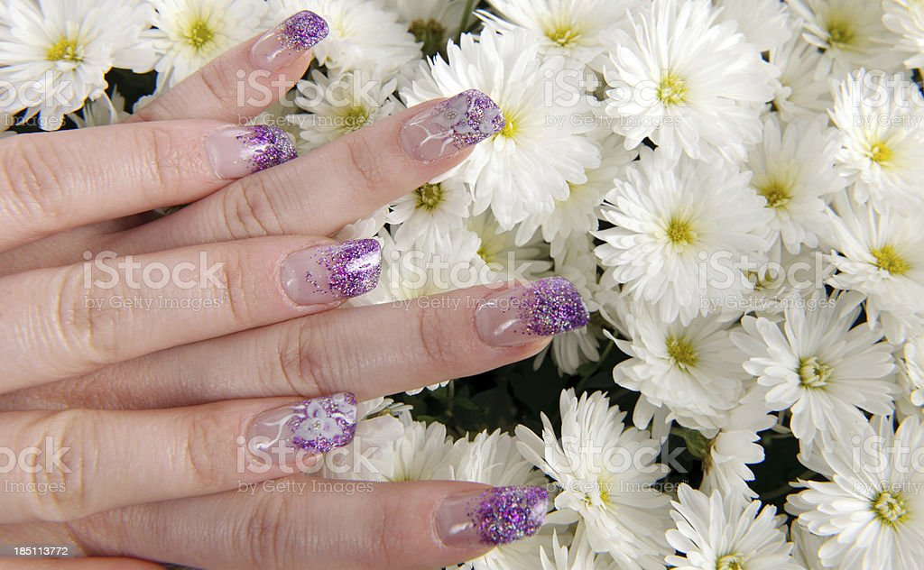 woman with purple nails on white daisy background flowers.