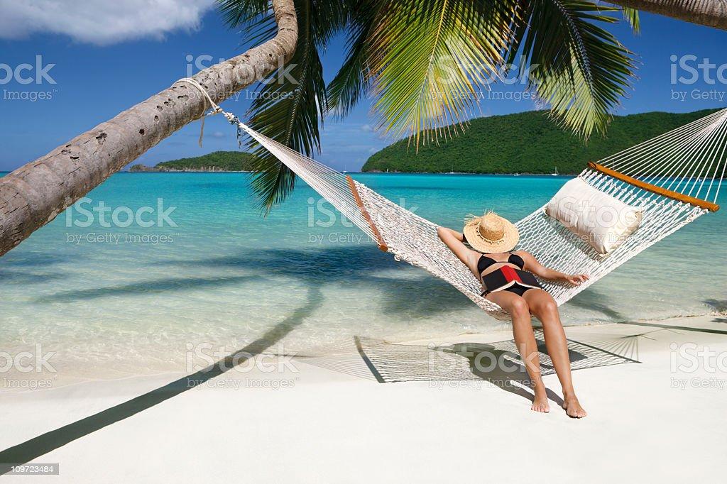 woman napping in hammock at a tropical Caribbean beach royalty-free stock photo