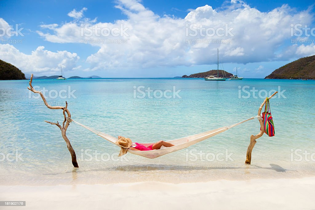 woman napping in hammock stretched between two pieces of driftwood royalty-free stock photo