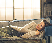 Woman napping on sofa in a city loft