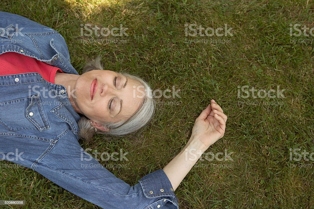 Woman napping outdoors stock photo