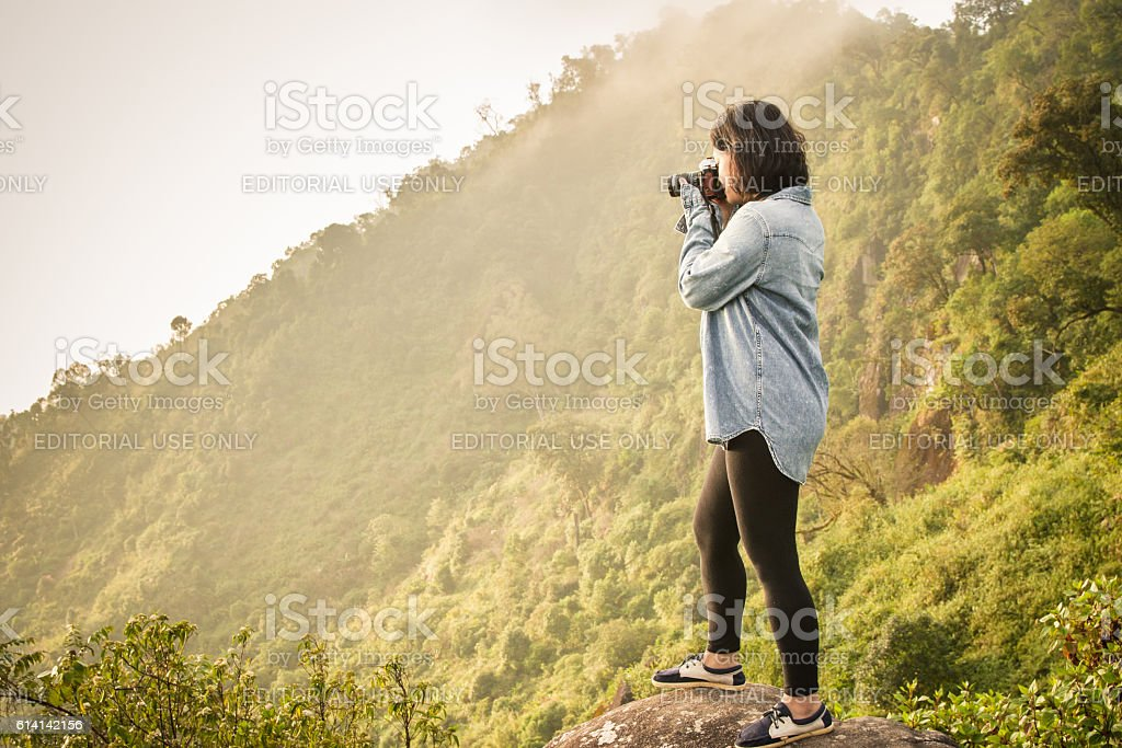 woman nature photographer taking pictures outdoors stock photo
