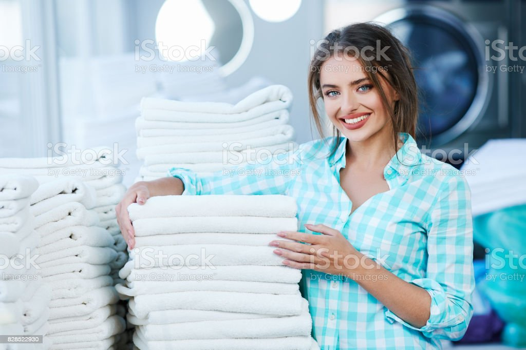 Woman near heaps of white clean linen stock photo