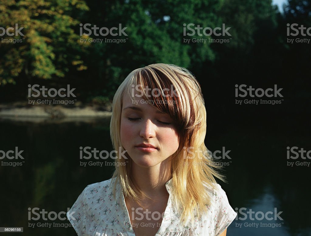 Woman near lake with her eyes closed royalty-free stock photo