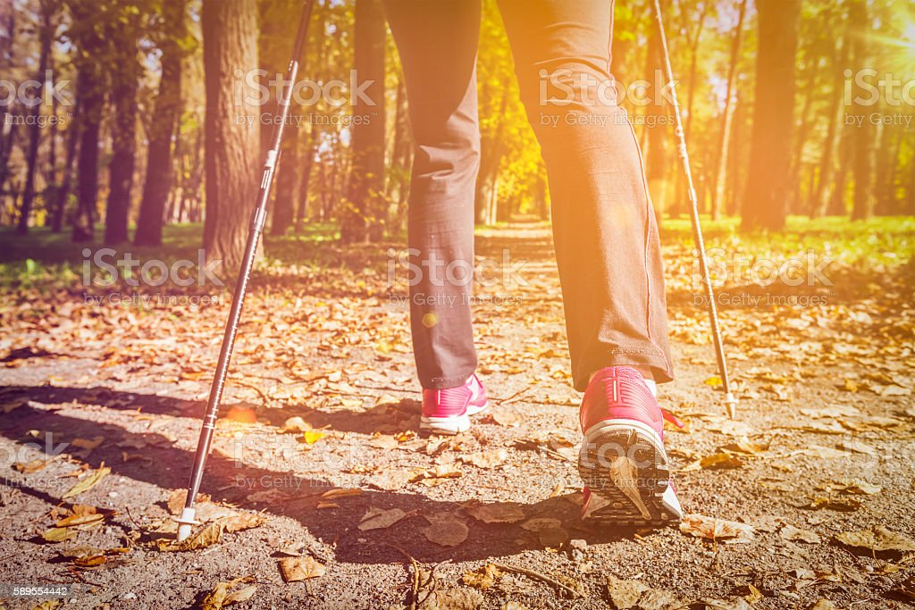 Woman nordic walking outdoors feet close up stock photo