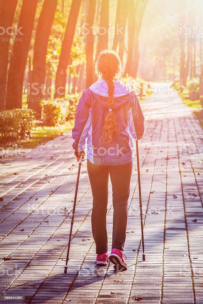 Woman nordic walking outdoors stock photo