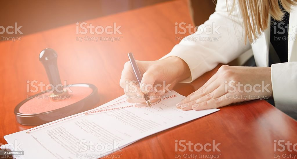 Woman Notary Public signing the contract stock photo