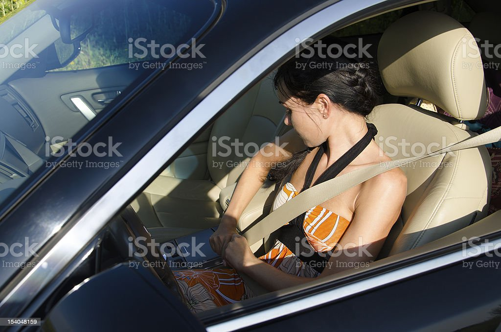 Woman obeying traffic rules tightening safety belt stock photo