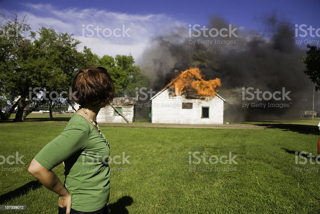 Woman observing house fire stock photo