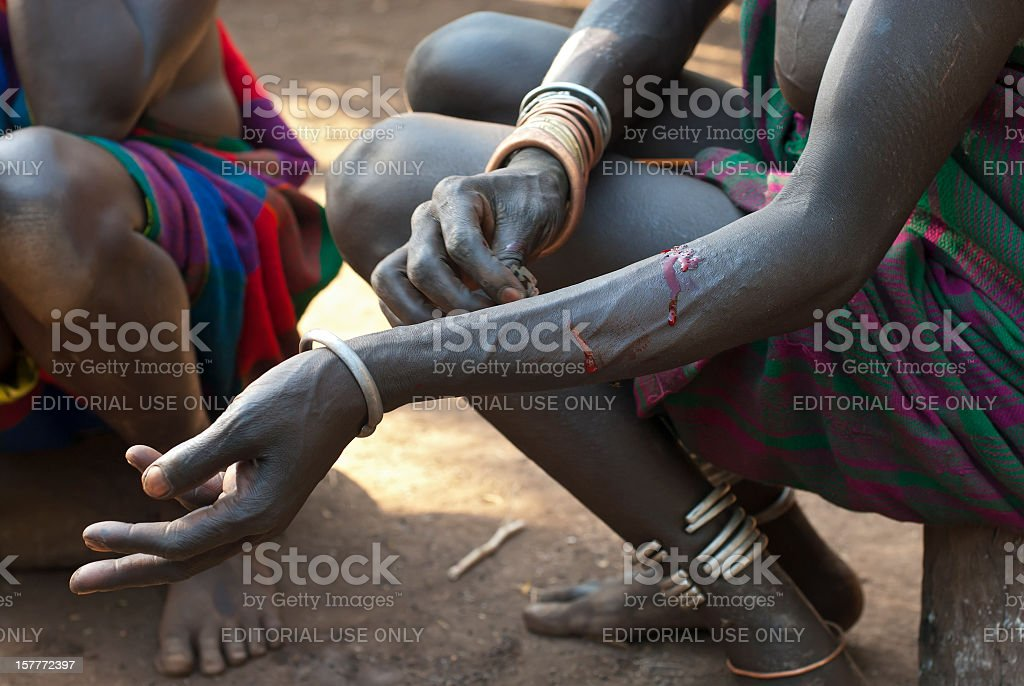 Woman of the Surma tribe in Ethiopia is cutting scars stock photo