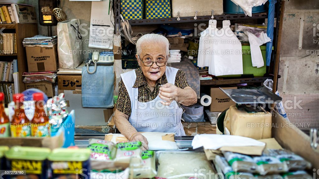 Woman offering a food sample Okinawa's Makeshi market. stock photo