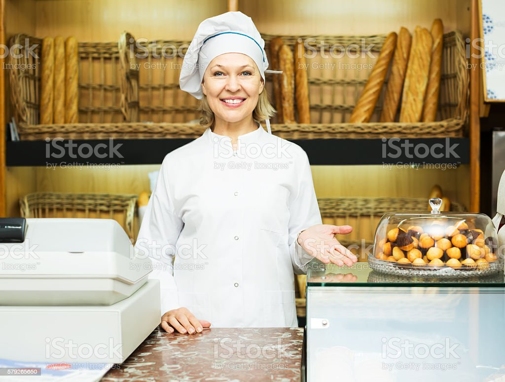 Woman offering bread in bakery stock photo