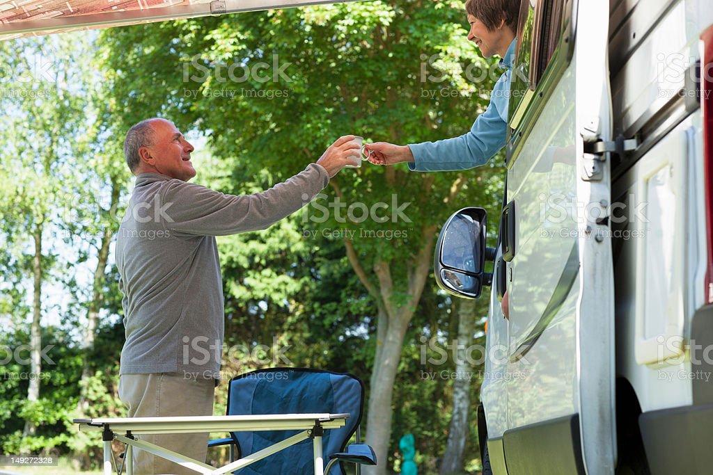 Woman offering man mug outside campervan stock photo