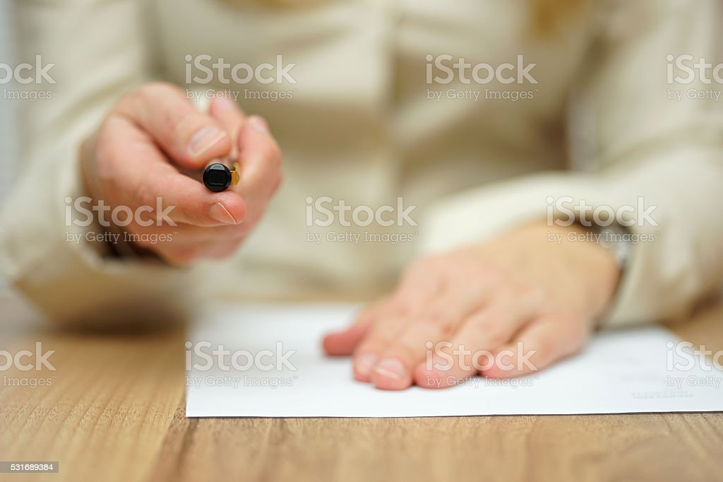 Woman offering pen to sign papers stock photo