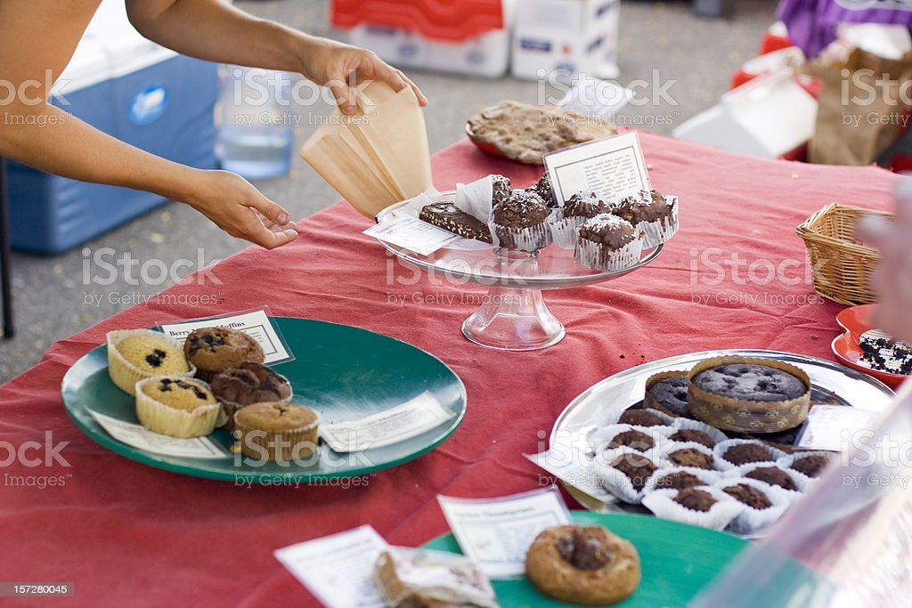 Woman offers fresh pastry at charity fundraiser bake sale royalty-free stock photo