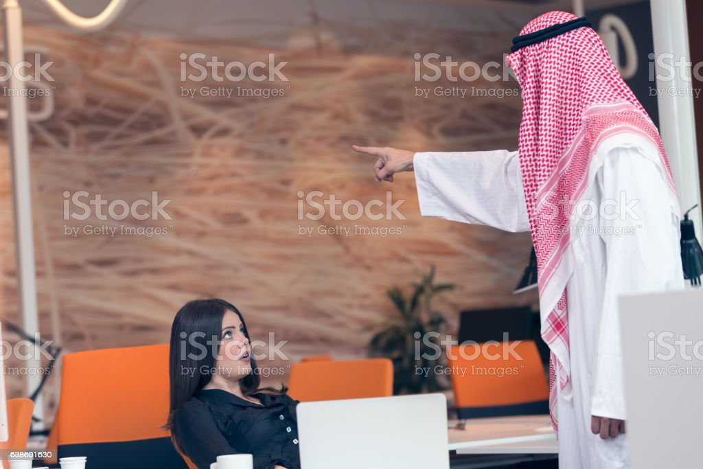 Woman office worker gets fired by arab businessman stock photo