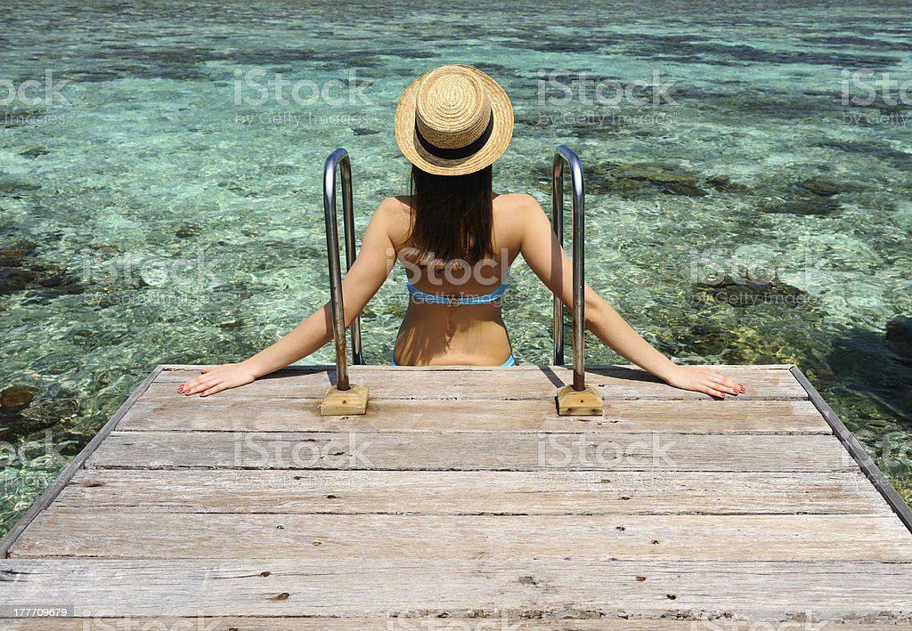 Woman on a beach jetty at Maldives royalty-free stock photo
