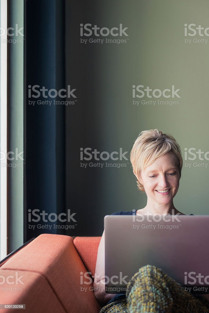 Woman On A Couch With Her Laptop stock photo