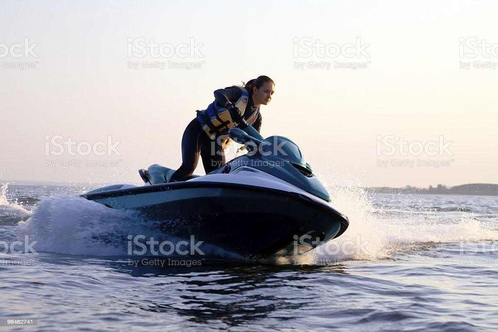 Woman on a jet ski in the ocean during the sunset stock photo