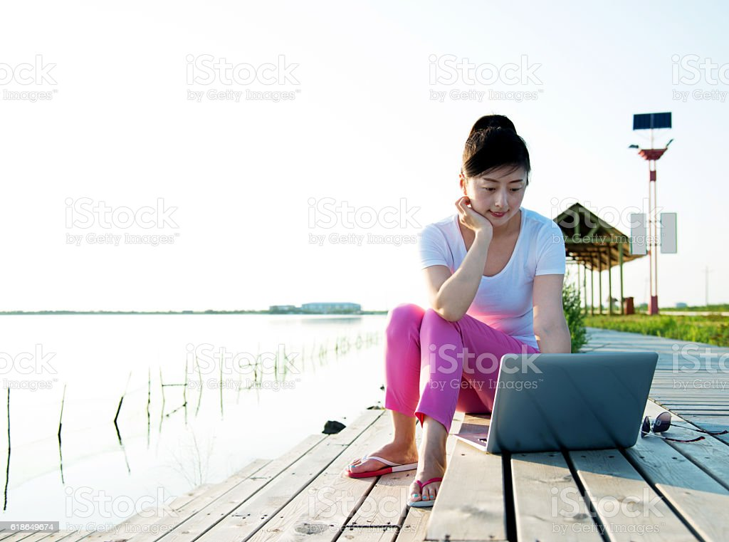 Woman on a jetty working outdoor stock photo